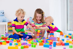 Kids playing with colorful toy blocks Stock Photos