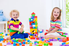 Kids playing with colorful toy blocks Stock Photography