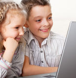 Kids playing computer. Children with laptop indoors. Happy kids playing computer at home Stock Photography