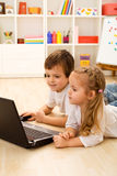 Kids playing computer game on laptop. Laying on the floor Stock Photography