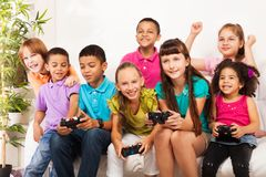 Kids playing computer games as team. Closeup portrait of group of diversity looking kids, boys and girls playing videogame sitting on the sofa in living room Royalty Free Stock Photo