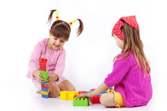 Kids playing with constructor. Portrait of two kids playing with constructor over white Royalty Free Stock Photos