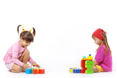 Kids playing with constructor. Portrait of two kids playing with constructor over white Royalty Free Stock Photography