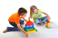 Kids playing with constructor. Kids boy and girl playing  and building house with constructor isolated on white background Stock Photos