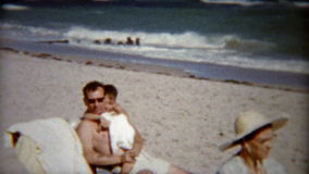 1959: Kids playing with dad and gives stoic grandma some love. MIAMI, FLORIDA. Vintage 8mm film home movie professionally cleaned and captured in 4k (3840x2160 stock footage
