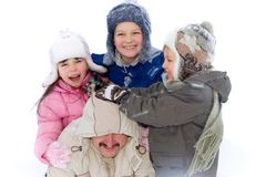 Kids Playing with Dad in the Snow. Three children outside playing in the winter snow with their father. Isolated on a white background Stock Image
