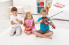 Kids playing on different musical instruments royalty free stock photos