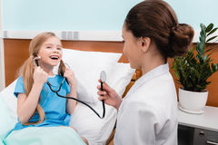 Kids playing doctor and patient with stethoscope in hospital. Happy kids playing doctor and patient with stethoscope in hospital Stock Photography