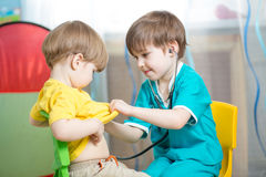 Kids playing doctor in playroom or kindergarten stock images