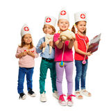 Kids playing doctor with toy medical instruments. Four little kids playing doctor with toy medical instruments, holding tooth and cerebrum models and x-ray royalty free stock images