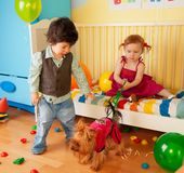 Kids playing with dog and having party Stock Photos