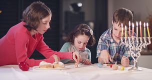 Kids playing with dreidels during Hanukka at home. Kids playing with toy dreidels during Hanukka at home stock footage