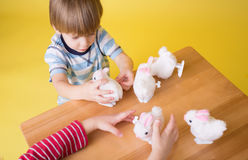 Kids playing with Easter Bunny Toys. Kids, children having fun and playing with wound up easter bunny toys royalty free stock photography