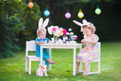 Kids playing Easter tea party with toys royalty free stock photos