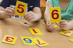 Kids are playing. Educational games. A child in kindergarten. The hands of a child. Maths. Cards for development royalty free stock photos