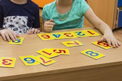 Kids are playing. Educational games. A child in kindergarten. The hands of a child. Maths. Cards for development royalty free stock photography