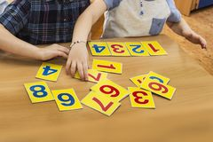 Kids are playing. Educational games. A child in kindergarten. The hands of a child. Maths. Cards for development stock photo