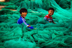 Kids playing in fishing nets. The colors of fishing nets in Vietnam are very vivid and create amazing textures, these kids where playing in the nets whilst the Royalty Free Stock Photo