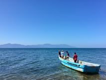 Kids playing and fishing on an old boat. In the ocean with mountains in the background in Honduras Stock Images