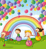 Kids playing with floating balloons and rainbow in the sky Royalty Free Stock Photography