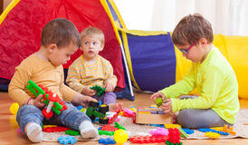 Kids playing on  floor. Two girls and boy with toys on  floor at home Stock Image
