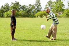 Kids playing football. Two African teen kids playing football in the park royalty free stock image
