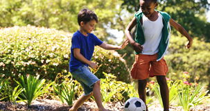 Kids playing a football in park stock video