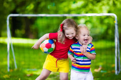 Kids playing football in a park. Two happy children playing European football outdoors in school yard. Kids play soccer. Active sport for preschool child. Ball stock image