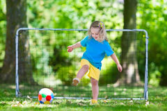Kids playing football in school yard. Little girl  playing European football outdoors in school yard. Kids play soccer. Active sport for preschool child. Ball Royalty Free Stock Photos