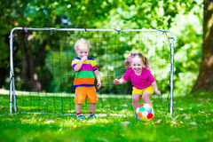 Kids playing football in school yard. Two happy children playing European football outdoors in school yard. Kids play soccer. Active sport for preschool child Stock Photo