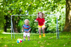 Kids playing football in school yard. Two happy children playing European football outdoors in school yard. Kids play soccer. Active sport for preschool child Stock Image