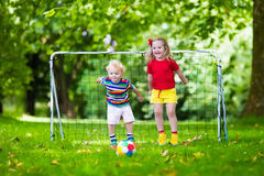 Kids playing football in school yard. Two happy children playing European football outdoors in school yard. Kids play soccer. Active sport for preschool child Royalty Free Stock Images