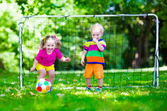 Kids playing football in school yard. Two happy children playing European football outdoors in school yard. Kids play soccer. Active sport for preschool child Stock Images