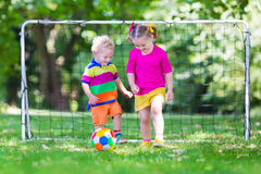 Kids playing football in school yard. Two happy children playing European football outdoors in school yard. Kids play soccer. Active sport for preschool child Royalty Free Stock Photography