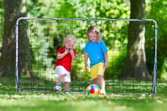 Kids playing football in school yard. Two happy children playing European football outdoors in school yard. Kids play soccer. Active sport for preschool child Royalty Free Stock Image