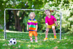 Kids playing football in school yard. Two happy children playing European football outdoors in school yard. Kids play soccer. Active sport for preschool child Stock Photos