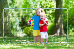 Kids playing football in school yard. Two happy children playing European football outdoors in school yard. Kids play soccer. Active sport for preschool child Stock Photography