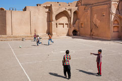 Kids playing football on the street Stock Image