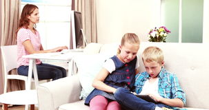 Kids playing games of the couch. With mother on her pc stock video footage