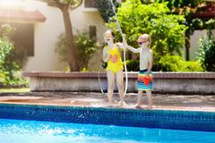Kids play with water hose at swimming pool. Kids playing with garden hose in backyard with large outdoor swimming pool. Children play with water. Swim wear and Stock Photography
