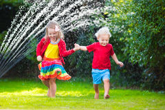 Kids playing with garden sprinkler. Child playing with garden sprinkler. Preschooler kid run and jump. Summer outdoor water fun in the backyard. Children play stock images