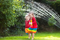 Kids playing with garden sprinkler Stock Photography