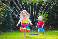 Kids playing with garden sprinkler. Child playing with garden sprinkler. Preschooler kid running and jumping. Summer outdoor water fun in the backyard. Children stock photo