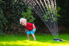 Kids playing with garden sprinkler Stock Photos