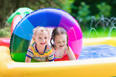 Kids playing in garden swimming pool Stock Images