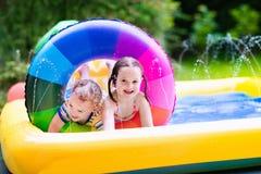 Kids playing in garden swimming pool Royalty Free Stock Photo