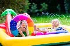 Kids playing in garden swimming pool Stock Photos