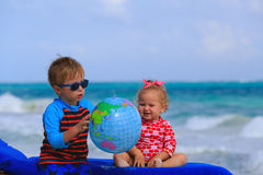Kids playing with globe on the beach, travel Royalty Free Stock Photography