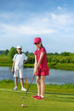 Kids playing golf. Girl playing golf and hitting by putter on green Stock Image