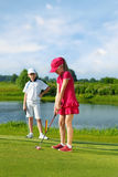 Kids playing golf. Girl playing golf and hitting by putter on green Stock Photography